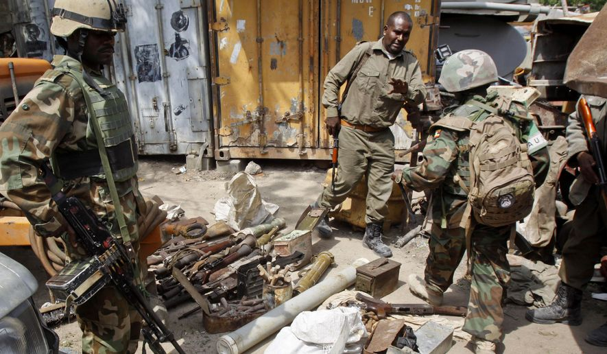 In this photo taken Sunday, July 27, 2014, African Union (AU) peacekeepers stand near a cache of weapons recovered from a garage in Mogadishu, Somalia. An official says that Somalia's government has launched a new disarmament campaign, that has netted some 500 guns during four raids, which is being carried out because officials fear that weapons could fall into the hands of al-Qaeda-linked fighters. (AP Photo/Farah Abdi Warsameh)