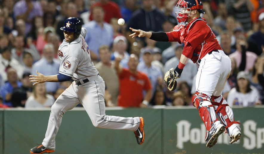 Houston Astros' Gregorio Petit, left, scores as Boston Red Sox's Christian Vazquez tosses to home plate after missing the tag during the eighth inning of a baseball game in Boston, Friday, Aug. 15, 2014. (AP Photo/Michael Dwyer)