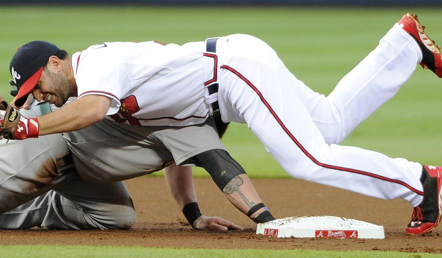 Atlanta Braves second baseman Phil Gosselin, right, falls onto Oakland Athletics' Jonny Gomes (15) after the pickoff at second base during the first inning of a baseball game against the Oakland Athletics Friday, Aug. 15, 2014, in Atlanta. The play was reviewed and the call was upheld for an out. (AP Photo/David Tulis)