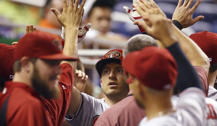 Arizona Diamondbacks' Cliff Pennington celebrates in the dugout after hitting a home run during the first inning of a baseball game in Miami against the Miami Marlins, Friday, Aug. 15, 2014.  (AP Photo/J Pat Carter)