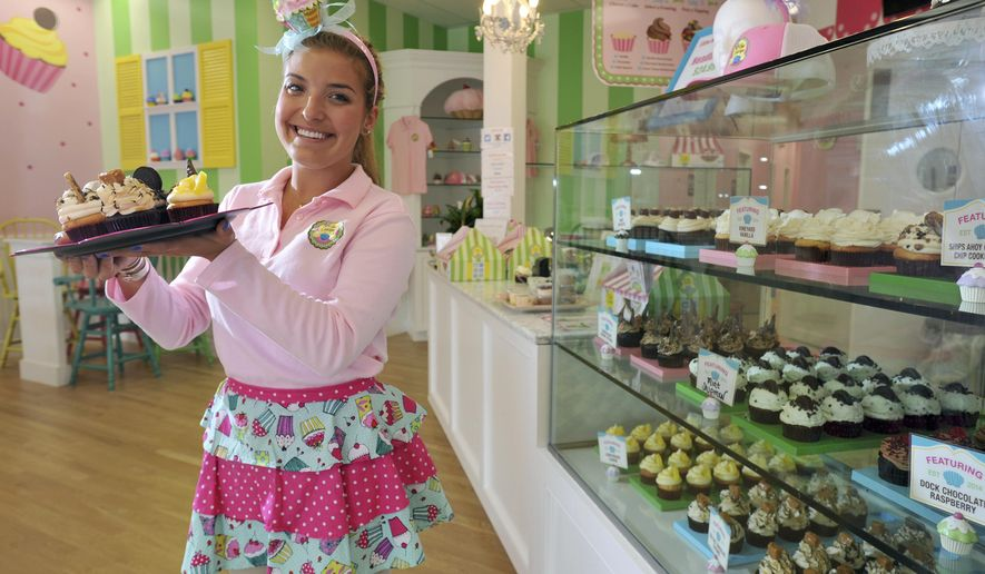 """AP MEMBER FEATURE EXCHANGE ADVANCE FOR AUG. 16 -- In this July 23, 2014 photo, owner Taylor Stump displays her cupcake masterpieces at the Little Miss Cupcape  bakery on Main Street Hyannis, Mass. Stump, dubbed """"the cupcake queen"""" in high school, graduated from college in May and opened her business the next month. (AP Photo/Cape Cod Times, Steve Heaslip)"""