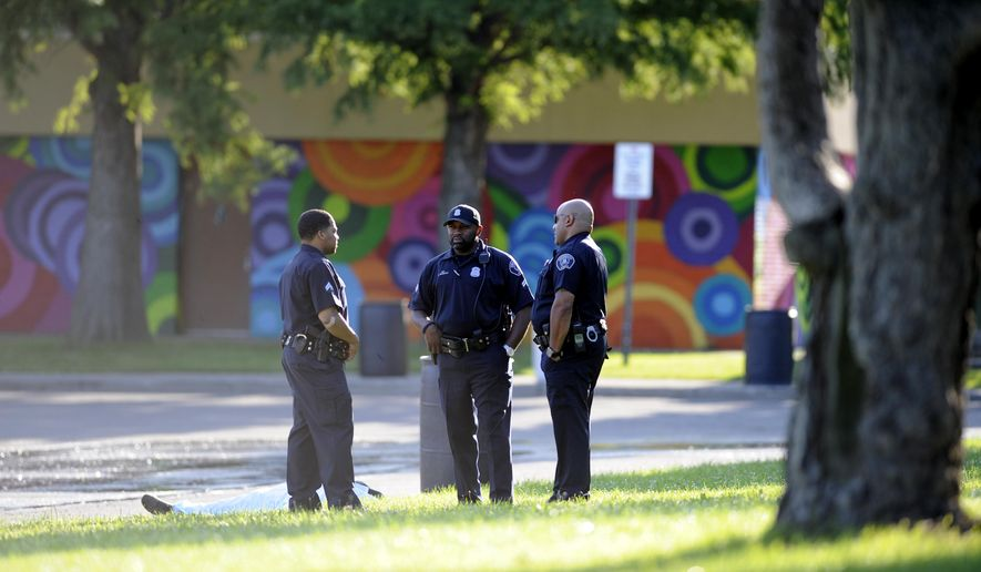 Detroit Police stand next to a body under a tarp in Palmer Park in Detroit on Friday, Aug. 15, 2014, during the investigation of a fatal shooting. (AP Photo/Detroit News, David Coates)  DETROIT FREE PRESS OUT; HUFFINGTON POST OUT, MANDATORY CREDIT, MAGS OUT