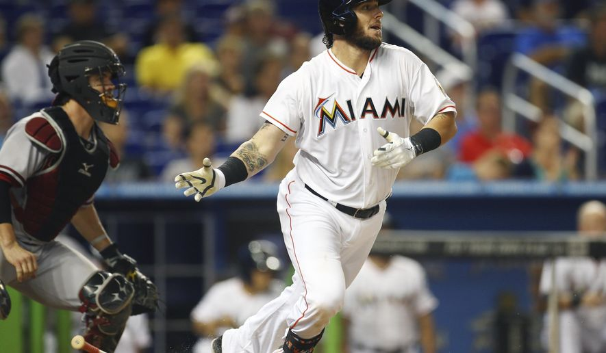 Miami Marlins's Jarrod Saltalamacchia hits into a double play in front of Arizona Diamondbacks catcher Tuffy Gosewisch to end the first inning of a baseball game in Miami, Friday, Aug. 15, 2014.  (AP Photo/J Pat Carter)