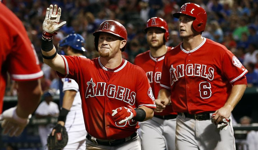Los Angeles Angels' Kole Calhoun, left, is congratulated as he heads to the dugout after hitting a three-run home run scoring David Freese (6) and Chris Iannetta against the Texas Rangers during the fifth inning of a baseball game, Friday, Aug. 15, 2014, in Arlington, Texas. (AP Photo/Jim Cowsert)