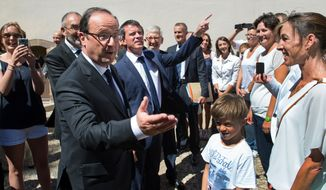 French President Francois Hollande, left, and French prime minister Manuel Valls chat with people as they arrive at the Fort de Bregancon, one of the official presidential residences since 1968, to take part in a working meeting, in Bormes-les-Mimosas, southern France, Friday Aug. 15, 2014. (AP Photo/Bertrand Langlois, Pool)