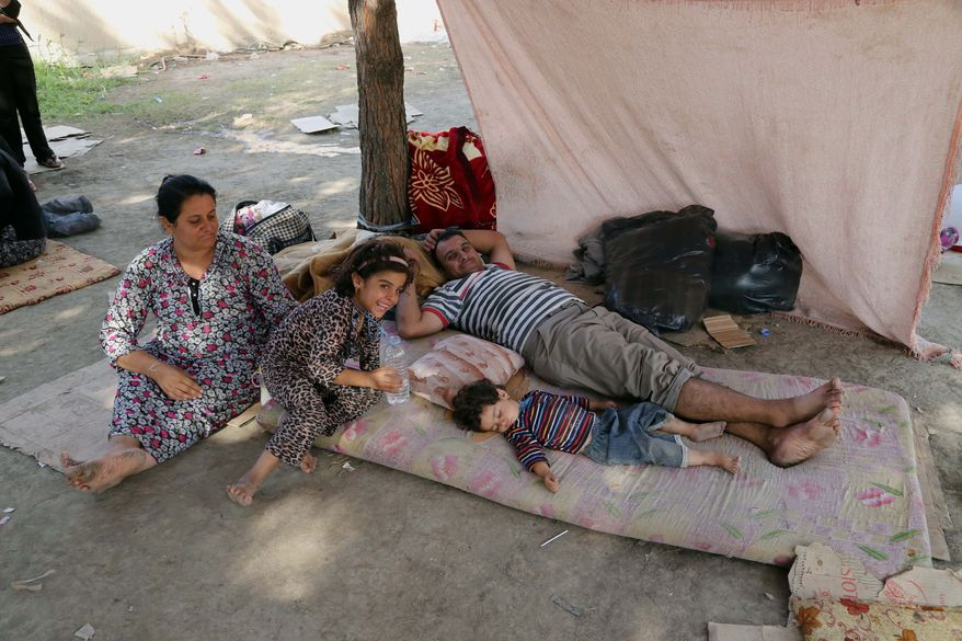 "Displaced Iraqis from the Yazidi community gather at a park near the Turkey-Iraq border at the Ibrahim al-Khalil crossing, as they try to cross to Turkey, in Zakho, 300 miles (475 kilometers) northwest of Baghdad, Iraq, Friday, Aug. 15, 2014. The U.N. this week declared the situation in Iraq a ""Level 3 Emergency"" — a decision that came after some 45,000 members of the Yazidi religious minority were able to escape from a remote desert mountaintop where they had been encircled by Islamic State fighters. The extremist group views them as apostates and had vowed to kill any who did not convert to Islam. (AP Photo/Khalid Mohammed)"