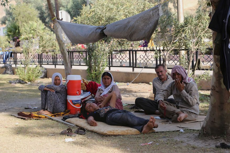 Displaced Iraqis from the Yazidi community gather at a park near the Turkey-Iraq border at the Ibrahim al-Khalil crossing, as they try to cross to Turkey, in Zakho, 300 miles (475 kilometers) northwest of Baghdad, Iraq, Friday, Aug. 15, 2014. The European Union on Friday forged a unified response to the rapid advance of Islamic militants in Iraq and the resulting refugee crisis, allowing direct arms deliveries to Kurdish fighters battling the Sunni insurgents, while several EU nations pledged more humanitarian aid. (AP Photo/Khalid Mohammed)