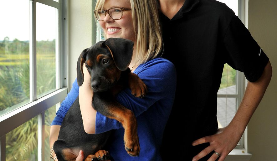Todd Blake, his wife Maja Blake and their new puppy Louie in their Ponte Vedra Beach, Fla., apartment.  Blake is a recent graduate of the University of Florida who graduated with a 4.0 GPA and is battling Stage IV Hodgkin's Lymphoma.  (The Florida Times-Union/Bob Self)