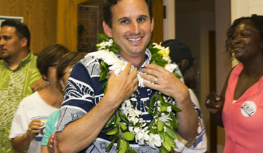 US Sen. Brian Schatz, center, celebrates with supporters after defeating fellow Democrat US Rep. Colleen Hanabusa to retain his senate seat, Friday, Aug. 15, 2014 in Hilo, Hawaii.  (AP Photo/Marco Garcia)