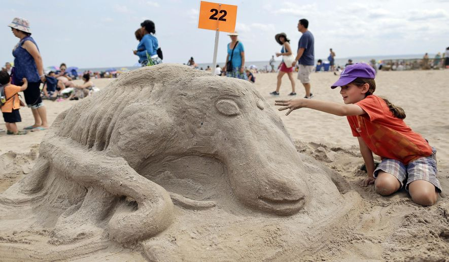 Ari Blumanfeld puts finishing touches on a sand sculpture on the beach during a sculpting contest in the Coney Island neighborhood in the Brooklyn borough of New York, Saturday, Aug. 16, 2014. Proceeds from the contest will go to help residents still rebuilding from Superstorm Sandy. (AP Photo/Julie Jacobson)