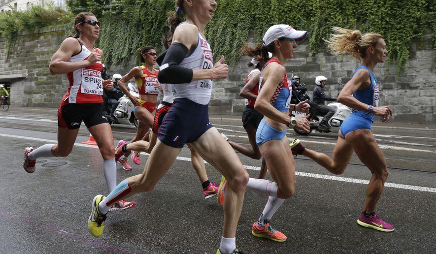 France's Christelle Daunay, center, runs in the women's marathon during the European Athletics Championships in Zurich, Switzerland, Saturday, Aug. 16, 2014. (AP Photo/Petr David Josek)