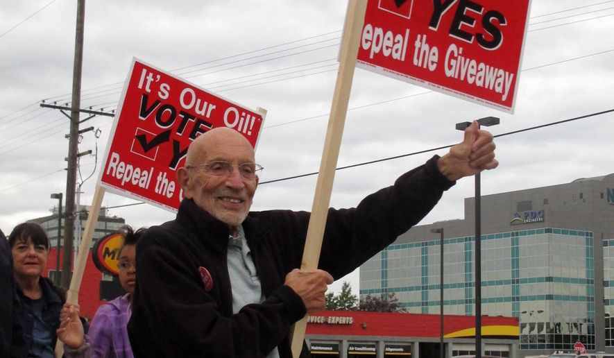 FILE - In this Aug. 8, 2014 file photo, Vic Fischer, a leader of the effort to repeal the oil tax system passed by Alaska state lawmakers in 2013, takes part in a sign-waving event on a busy street in Anchorage, Alaska. Alaskans head to the polls Tuesday, Aug. 19, 2014, to decide if the state's old system for taxing oil companies, passed in 2007 after some lawmakers were suspected of bribery, is better than the new system, a tax cut passed last year to try to attract investment from petroleum companies. (AP Photo/Becky Bohrer, File)