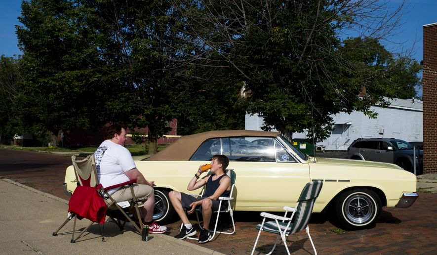 Tyler Tuppett, 22, of Flint, left, looks up from his cell phone to talk to his cousin Seth Provorse, 14, while the two sit with the 1965 Buick Special, owned by Burton resident and their grandfather Al Jones, as it is parked for display during Back to the Bricks on Saturday, Aug. 16, 2014, in Flint, Mich. Buicktown, a chapter of Buick Club of America, set up to pay homage to where Buick was founded, setting up on the street where it all started. (AP Photo/The Flint Journal, Jake May) LOCAL TELEVISION OUT; LOCAL INTERNET OUT