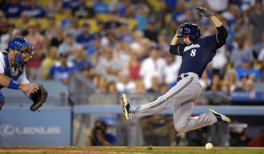 Milwaukee Brewers' Ryan Braun, right, scores on a single by Scooter Gennett as Los Angeles Dodgers catcher A.J. Ellis takes a late throw during the eighth inning of a baseball game, Friday, Aug. 15, 2014, in Los Angeles. (AP Photo/Mark J. Terrill)