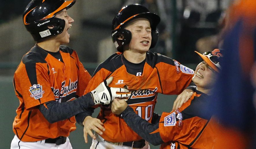 Cumberland's CJ Davock, center, celebrates his walkoff-double with teammates Addison Kopack, left, and Brendan Wright, right, in the sixth inning of a baseball game against Nashville at the Little League World Series tournament in South Williamsport, Pa., Saturday, Aug. 16, 2014. Cumberland won 8-7. (AP Photo/Gene J. Puskar)