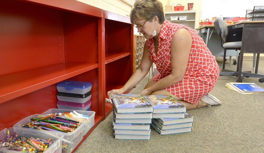 Homer Community School teacher Gaylene Kunzie wipes down shelves while preparing her classroom on Wednesday, Aug. 6, 2014, for next week's start to the new school. Kunzie, a 36-year veteran teacher is returing to her alma mater to teach sixth-grade. (AP Photo/The Sioux City Journal, Tim Hynds)