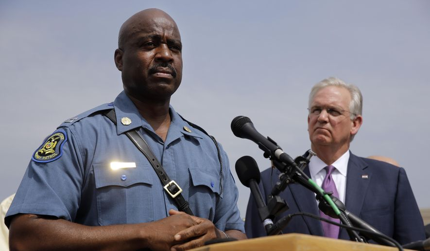 Missouri Gov. Jay Nixon, right, assigned Missouri Highway Patrol Capt. Ron Johnson, left, to defuse violent protests sparked by the fatal shooting of Michael Brown by a police officer. (AP Photo/Jeff Roberson, File)