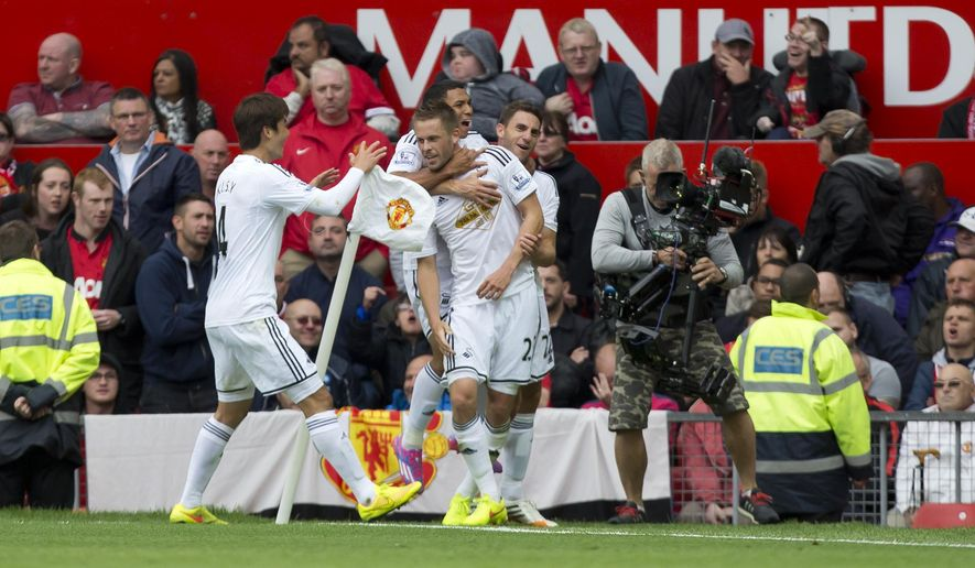 Swansea City's Gylvi Sigurdsson, lower center, celebrates with teammates after scoring against Manchester United during their English Premier League soccer match at Old Trafford Stadium, Manchester, England, Saturday Aug. 16, 2014. (AP Photo/Jon Super)