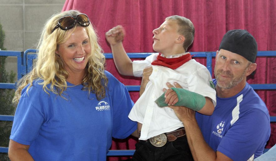 This Aug. 9, 2014 photo provided by Steve Bell, shows buyers, Mike and Tammy McKean, with Tucker Doak at the Weber County Fair in Ogden, Utah. The crowd erupted in applause and began chanting his name as 13-year-old Tucker Doak entered the ring at Weber County's Fair to auction off his hog. This was the Doak's family first year participating in the fair's 4-H Junior Livestock program. (AP Photo/Steve Bell)