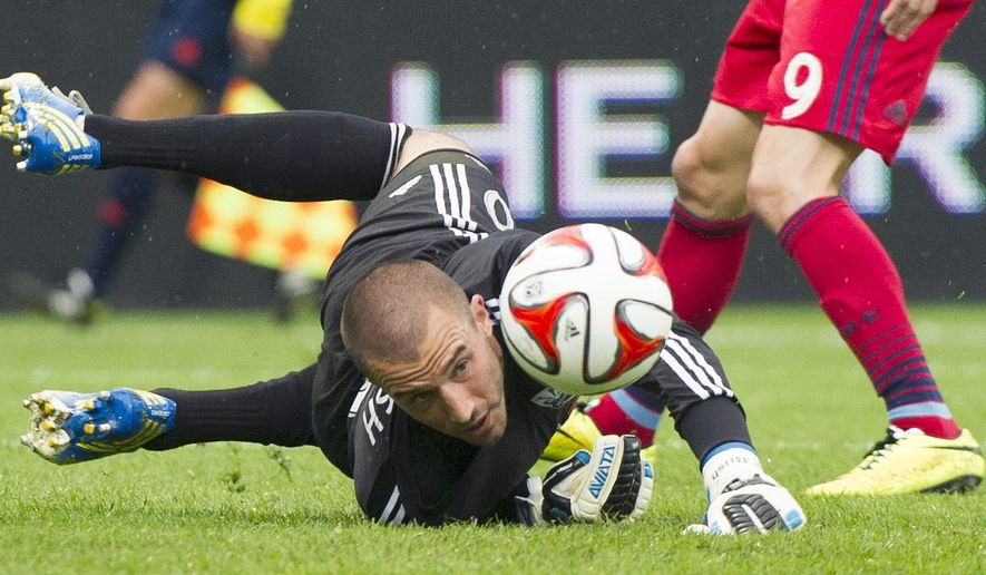 Montreal Impact goalkeeper Evan Bush keeps his eyes on the ball as Chicago Fire's Mike Magee (9) moves in during the first half of an MLS soccer game Saturday, Aug. 16, 2014, in Montreal. (AP Photo/The Canadian Press, Graham Hughes)