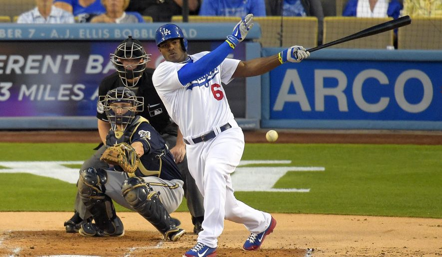 Los Angeles Dodgers' Yasiel Puig, right, hits an RBI single as Milwaukee Brewers catcher Jonathan Lucroy, left, and home plate umpire Toby Basner watch during the first inning of a baseball game, Friday, Aug. 15, 2014, in Los Angeles. (AP Photo/Mark J. Terrill)