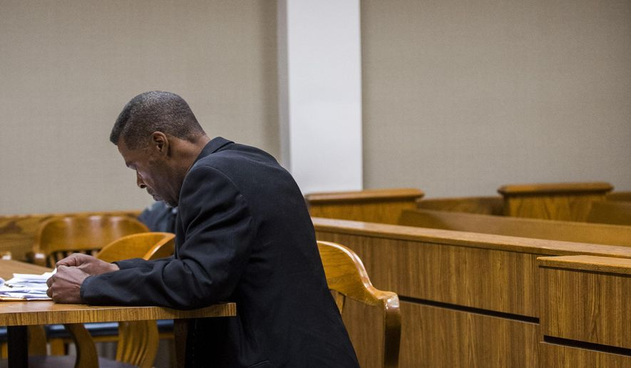 In this photo taken on Friday, Aug. 15, 2014, Flint City Councilman Eric Mays bows to his knees as he prays before his sentencing hearing in Flint, Mich., where he was sentenced to 72 days in jailfor impaired driving. A jury in June found Mays not guilty of operating a vehicle while intoxicated, marijuana possession and refusing to be fingerprinted. The jury replaced the operating a vehicle while intoxicated charge with driving while impaired and convicted him on that charge. (AP Photo/The Flint Journal, Jake May) LOCAL TELEVISION OUT; LOCAL INTERNET OUT