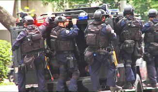 In this July 6, 2013 still frame from a video produced by the Los Angeles Police Department, officers ride on an armored medical rescue vehicle in a drill simulating a terrorist attack in downtown Los Angeles. After spending a decade sending military equipment to civilian police departments across the United States, Washington is reconsidering the idea in light of the violence in Ferguson, Mo., amid images of heavily-armed police, snipers trained on protesters and tear gas plumes. One night after the violence that accompanied the presence of military-style equipment in Ferguson, the crowd calmed considerably when a police captain walked through the crowd, unprotected, in a gesture of reconciliation. The contrast added to the perception that the tanks and tear gas had done more harm than good. (AP Photo/Los Angeles Police Department)