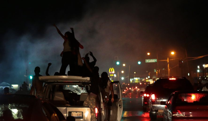 Smoke from a tire burnout rises over protestors on West Florissant Avenue in Ferguson on Friday, Aug. 15, 2014.   (AP Photo/St. Louis Post-Dispatch, Robert Cohen)