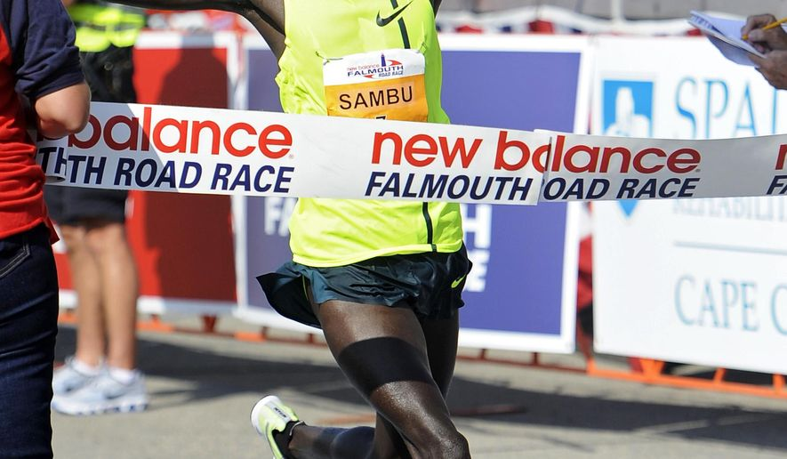 Stephen Sambu, 26, of Kenya crosses the finish line as the first place winner during the 42nd Falmouth Road Race on Sunday, Aug. 17, 2014, in  Falmouth, Mass. More than 12,000 runners participated in the annual event. (AP Photo/The Cape Cod Times, Christine Hochkeppel)