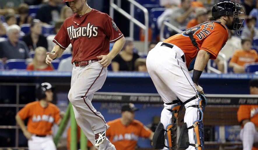 Arizona Diamondbacks' Ender Inciarte, left, scores on a double hit by Mark Trumbo in the sixth inning during a baseball game against the Miami Marlins, Sunday, Aug. 17, 2014, in Miami. At right is Miami Marlins catcher Jarrod Saltalamacchia, (AP Photo/Lynne Sladky)