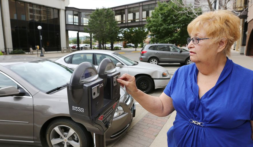Sharon Swanson puts money in a parking meter in downtown Sioux City Tuesday, July 19, 2014. (Jim Lee, Sioux City Journal)