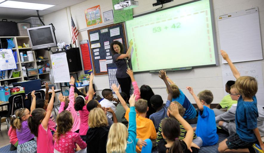 FILE - In this Oct. 1, 2013, file photo, third grade teacher Melissa Grieshober teaches a math lesson at Silver Lake Elementary School in Middletown, Del. Sometime in elementary school, you quit counting your fingers and just know the answer. Now scientists have put youngsters into brain scanners to find out why, and watched how the brain reorganizes itself as kids learn math. (AP Photo/Steve Ruark, File)