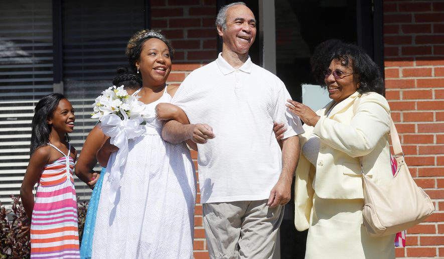 Miriam Reeves is escorted down the aisle by her father  Bernard Reeves, 64, who has Alzheimer's, and her mother Marie Reeves, right, during the Reeves / Davis wedding at Foundation Park Alzheimer's Care in Toledo, Ohio, Saturday, Aug. 16, 2014. Reeves wanted the ceremony to take place beneath the gazebo in the courtyard of the facility so that her father could participate in the happy affair. Niece Autumn Reeves, 8, left, watches. (AP Photo/The Toledo Blade, Amy E. Voigt) MANDATORY CREDIT, MAGS OUT, NO SALES, TV OUT, BOWLING GREEN SENTINEL-TRIBUNE, MONROE EVENING NEWS AND THE TOLEDO FREE PRESS OUT
