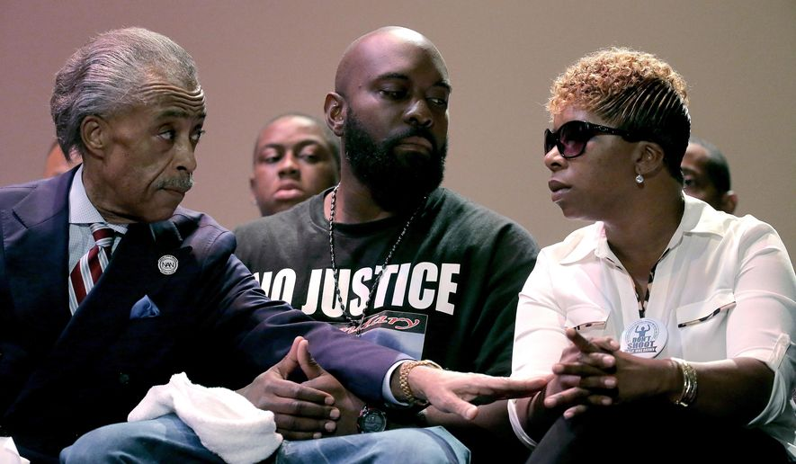 Rev. Al Sharpton speaks with parents of Michael Brown, Michael Brown Sr. and Lesley McSpadden during a rally at Greater Grace Church, Sunday, Aug. 17, 2014, for their son who was killed by police last Saturday in Ferguson, Mo. Brown's shooting in the middle of a street, following a suspected robbery of a box of cigars from a nearby market, has sparked a week of protests, riots and looting in the St. Louis suburb. (AP Photo/Charlie Riedel)