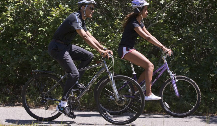President Barack Obama bike rides with daughter Malia Obama on the Manuel F. Correllus State Forest bike path, Friday, Aug. 15, 2014, outside of West Tisbury, Mass., during the Obama family vacation on the island of Martha's Vineyard. (AP Photo/Jacquelyn Martin)
