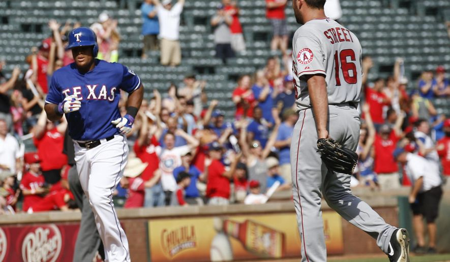 Texas Rangers' Adrian Beltre, left, runs home to score the winning run on a walkoff-single hit by Adam Rosales in front of Los Angeles Angels relief pitcher Huston Street (16) during the ninth inning of a baseball game, Sunday, Aug. 17, 2014, in Arlington, Texas. The Rangers won 3-2. (AP Photo/Jim Cowsert)