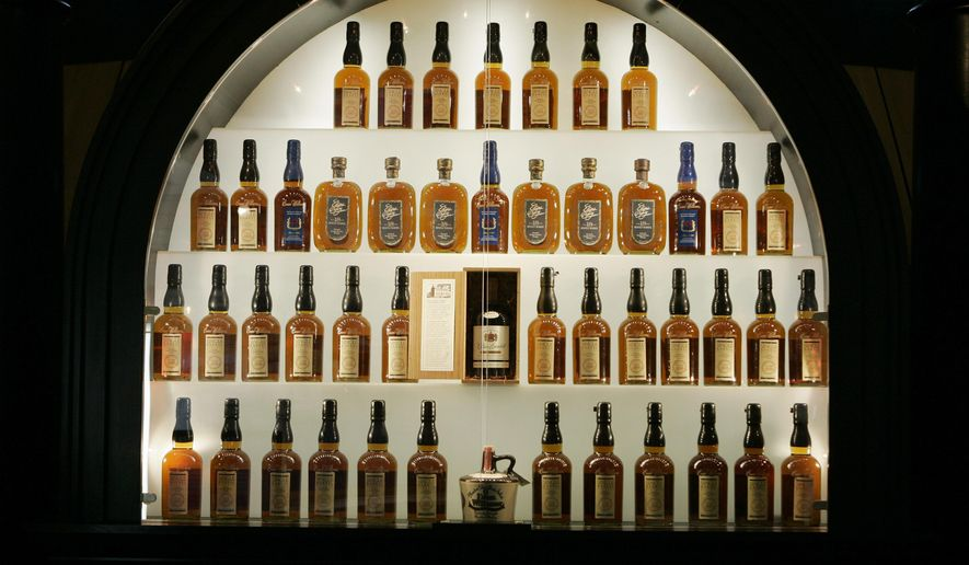 FILE - In this Wednesday, April 8, 2009, file photo, bottles of bourbon are on display in a case at the Heaven Hill Bourbon Heritage Center in Bardstown, Ky. Kentucky bourbon makers have stashed away their largest stockpiles in more than a generation due to resurgent demand for the venerable brown spirit. (AP Photo/Ed Reinke, File)