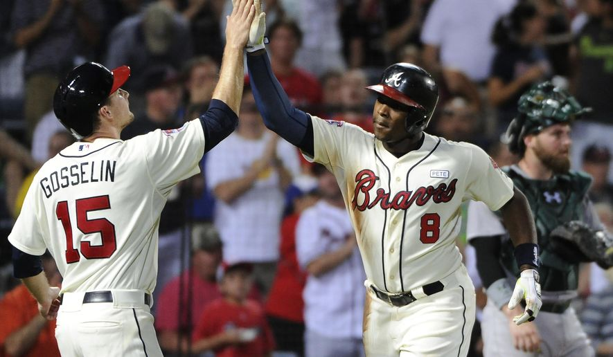 Atlanta Braves' Justin Upton, right, is congratulated by Phil Gosselin, who also scored on Upton's two-run homer, during the fourth inning of a baseball game against the Oakland Athletics Sunday, Aug. 17, 2014, in Atlanta. (AP Photo/David Tulis)