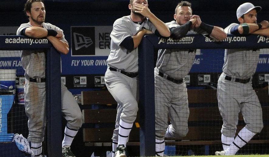 The Oakland Athletics watch from their dugout during the ninth inning of a baseball game against the Atlanta Braves Saturday, Aug. 16, 2014, in Atlanta. Atlanta won 4-3. (AP Photo/David Tulis)