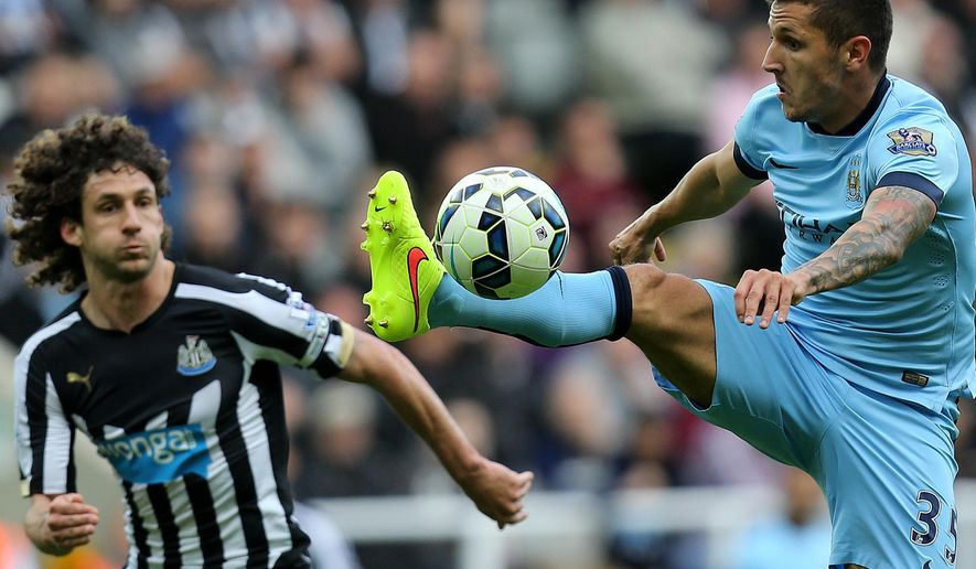 Manchester City's Steven Jovetic, right, vies for the ball with Newcastle United's captain Fabricio Coloccini, left, during their English Premier League soccer match at St James' Park, Newcastle, England, Sunday, Aug. 17, 2014. (AP Photo/Scott Heppell)