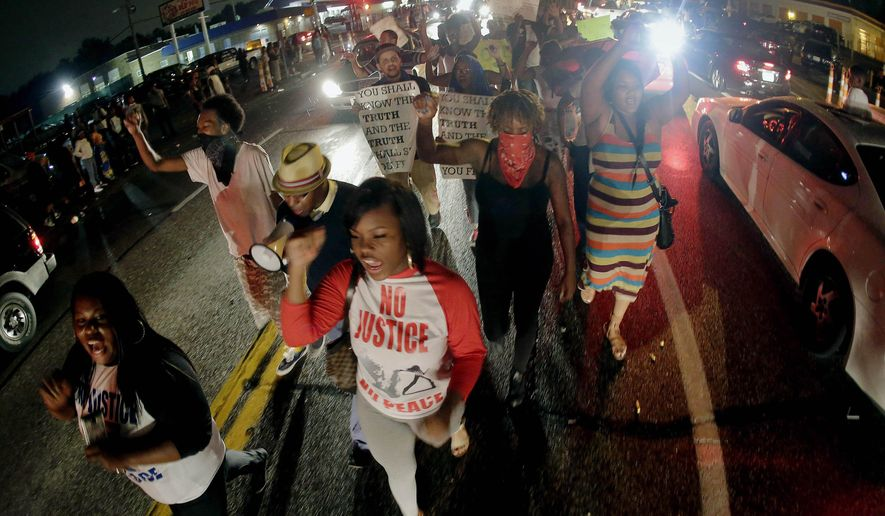 FILE - In this Friday, Aug. 15, 2014 file photo, protesters march down the middle of a street in front of a convenience store in Ferguson, Mo. that was looted and burned following the shooting death of Michael Brown, an unarmed black teenager, by a white police officer on Saturday, Aug. 9, 2014. Demonstrators are demanding justice for the 18-year-old Brown, which they say can only be accomplished if Ferguson police officer Darren Wilson is charged and convicted for the shooting. Many also cite larger causes. (AP Photo/Charlie Riedel)