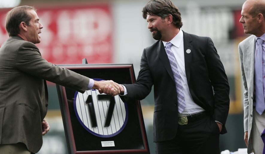 Colorado Rockies co-owners Dick, left, and Charlie Monfort, right, congratulate retired first Rockies first baseman Todd Helton during a ceremony to retire his number before the Rockies baseball game the Cincinnati Reds in Denver on Sunday, Aug. 17, 2014. (AP Photo/David Zalubowski)