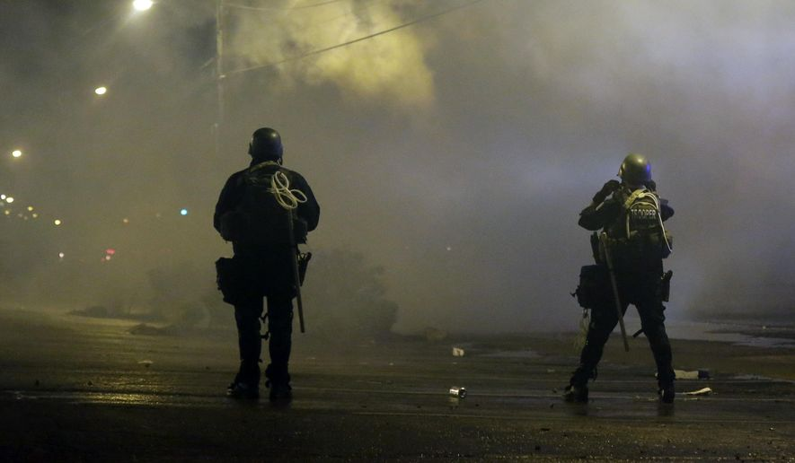 Tear gas is fired to disperse a crowd protesting the shooting of teenager Michael Brown last Saturday in Ferguson, Missouri. Brown's shooting in the middle of a street following a suspected robbery of a box of cigars from a nearby market has sparked a week of protests, riots and looting in the St. Louis suburb. (AP Photo/Charlie Riedel)