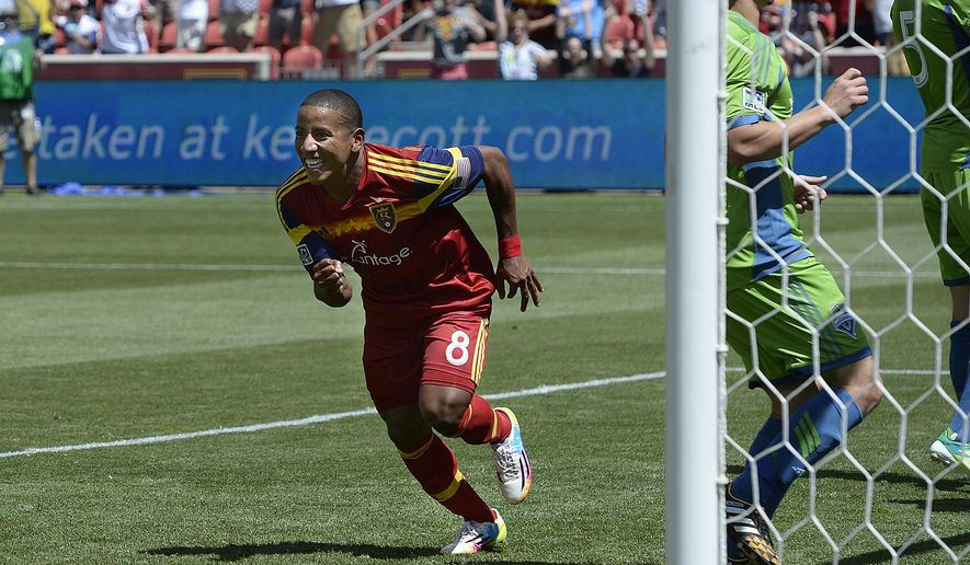 """Real Salt Lake forward Joao Plata rushes to congratulate Luke Mulholland after Mulholland's shot gave the team a 2-0 lead early in the second half against the Seattle Sounders in an MLS soccer game Saturday, Aug. 16, 2014. The goal was listed as an """"own goal"""" on Seattle's Osvaldo Alonso. (AP Photo/The Salt Lake Tribune, Scott Sommerdorf)"""