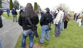 FILE - In this Feb. 8, 2013 file photo, Laura Huff, left, of Lacey, Wash., and Mike McCoy, second from right, wear M4 rifles during a gun rights rally at the Capitol in Olympia, Wash. While voters won't weigh on in two competing gun-related ballot measures for months, money is already pouring into the campaigns in advance of the November election.  (AP Photo/Ted S. Warren, File)
