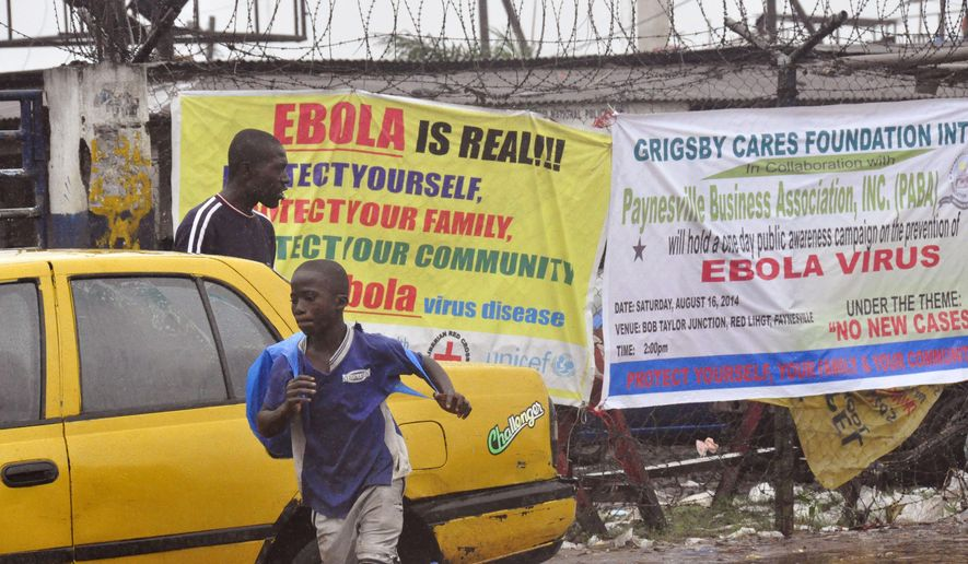 People pass by Ebola virus health warning signs, in the city of Monrovia, Liberia. Liberian officials fear Ebola could soon spread through the capital's largest slum after residents raided a quarantine center for suspected patients and took items including bloodstained sheets and mattresses. (AP Photo/Abbas Dulleh)