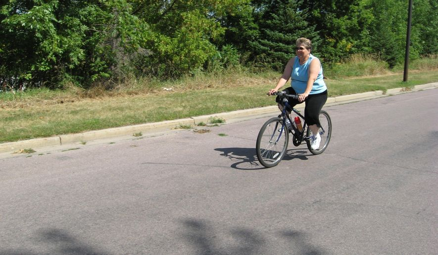 """In a Aug. 13, 2014 photo, Denise Leitz of New Ulm, Minn., rides her bike in New Ulm, Minn. Leitz never used to exercise. But after joining the Heart of New Ulm project she has made it a priority to squeeze in an hour-and-a-half bike ride most days. Of her new routine, the 56-year-old Leitz says """"It's as important to me as brushing my teeth every day. I just have to (do it). It just makes me feel so much better."""" (AP Photo/MPR News, Lorna Benson)"""