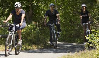 FILE - In this Aug. 15, 2014, file photo, first lady Michelle Obama, left, bikes rides with President Barack Obama and daughter Malia Obama on the Manuel F. Correllus State Forest bike path outside of West Tisbury, Mass., during the Obama family vacation on the island of Martha's Vineyard. Obama arrived on the Massachusetts island of Martha's Vineyard with one daughter, and the other daughter may be at his side when his two-week getaway ends later this month. In a first for Obama family summer vacations, neither teenager is spending the entire time with her father. (AP Photo/Jacquelyn Martin, File)