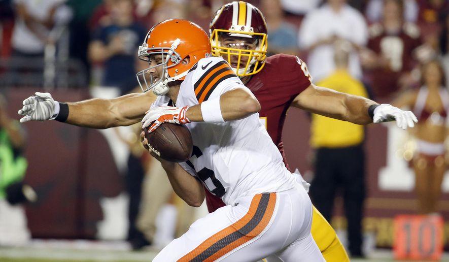 Washington Redskins outside linebacker Ryan Kerrigan sacks Cleveland Browns quarterback Brian Hoyer during the first half of an NFL preseason football game Monday, Aug. 18, 2014, in Landover, Md. (AP Photo/Alex Brandon)