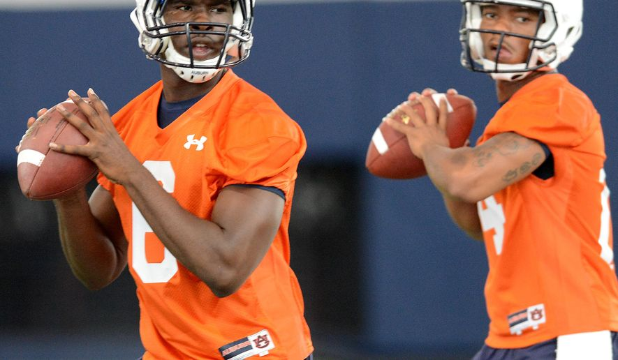 FILE - In this Aug. 2, 2013, file photo, Auburn quarterbacks Jeremy Johnson (6) and Nick Marshall (14) warm up during the first day of NCAA college football practice in Auburn, Ala.  Johnson says he has no idea if he's starting against Arkansas with starter Nick Marshall being held out for at least the opening. He does have one prediction: Marshall will win the Heisman Trophy. (AP Photo/AL.com, Julie Bennett, File) MAGS OUT